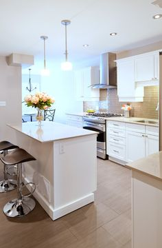 Beige walls, a white kitchen island and tiled flooring.