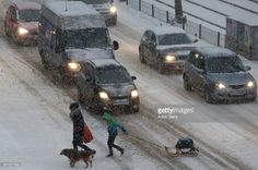 A woman with a dog and a child pulling a sled walk across a street during heavy snowfall on January 11, 2017 in Berlin, Germany. Cold weather has spread across Europe this week, with temperatures reaching as low as -30 Celsius (-22 Fahrenheit) and snow falling across the European continent from Ireland to the beaches of Greece. Over 30 deaths have been reported due to the cold, including several in Italy, the Czech Republic, Russia and Ukraine, as well as those of three migants, one Iraqi…