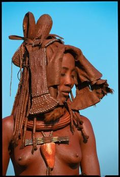 A young Himba bride, in a ceremonial headdress (Ekori) made of soft leather an covered with Ocher, butterfat and decorated with beads (Beckwith / Fisher)