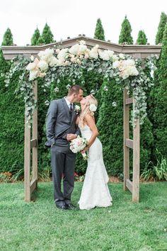 white hydrangeas, eucalyptus leaves wooden wedding arch