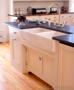 #Kitchen Idea of the Day: A traditional kitchen island with an apron sink, bridge-style faucet, soapstone countertops, and inset cabinets. Victorian kitchen by Crown Point Cabinetry