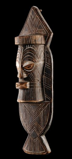 "Africa | Plank mask from the Songye people of DR Congo | Wood, black paint, kaolin | They have a dual function: first as a dance mask and secondly as an emblem of the ""bifwebe"" association to be hung to a wall or fence."
