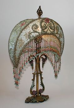 1920s Art Nouveau table lamp holds a French Blue Crescent shade covered in metallic lace and overlaid all overwith ornate scrolling appliques. Hand beaded fringe with vintage tube beads in matching tones adorns the bottom of the shade.