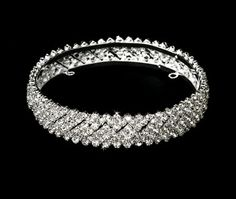 """This fully enclosed bun wrap boasts rows of sparkling rhinestones and adding a perfect touch of dazzle to your wedding day.   The piece measures 4-¼ """" in diameter and 1"""" in height, and features four concealed loops that allow you to fasten it in your hair with bobby pins. Price:$119.00"""