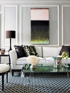 This sophisticated black and white living room mixes Hollywood glam with modern aesthetics. The white sofa with black piping lends an art deco vibe while the Lucite and mirrored coffee table is all modern.  White molding on gray textured walls provides a sophisticated background while the geometric rug anchors the space with a fun pattern.