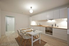 Very minimalistic kitchen--again, with the white contrasted with the golden natural wood. Lovely!