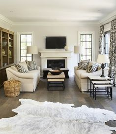 neutral living room, tv above fireplace, dark floors, white animal rug, furniture arrangement, baskets, zebra pilllows  PERFECTION!