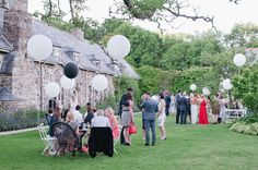 Country outdoor drinks reception with giant back & white ono balloons - Image by Rosie Anderson - Elegant Barn Wedding At The Great Barn Devon With Bride In Lusan Mandongus And Groom In Bespoke Dress 2 Kill Suit With Giant Cream And Black Balloons For Decor And Bridesmaids In Black Coast Dresses