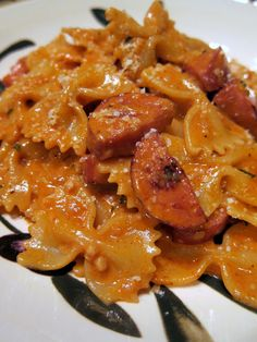Creamy Jambalaya Pasta: 1/2 pound Farfalle pasta; 1/2 lb smoked sausage, cut into bite-size pieces; 1 cup heavy cream (or half  half or evaporated milk); 2 tablespoons minced garlic; 1/4 cup chopped onion or 2 Tbsp minced onion flakes; 1 1/2 teaspoons Cajun seasoning; 1 1/2 teaspoons smoked paprika; 1 teaspoon salt  1/2 teaspoon pepper; 1/2 cup white wine; 4 tablespoon tomato sauce; 1 1/2 teaspoons chopped parsley; Parmesan cheese