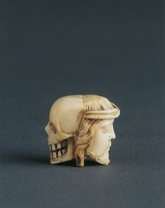 A 17th-century Italian carved ivory rosary bead; portrays a skull on one side and Christ's head on the other.