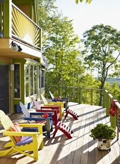 Adirondack chairs painted in different bright colors, with stripey pillows. Nice zing of color on the deck! | 10 inviting decks | Living the Country Life | http://www.livingthecountrylife.com/homes-acreages/country-homes/10-inviting-decks/
