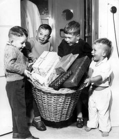 Walter Blum | Sinterklaas: vier kinderen met grote rieten mand vol sinterklaaskadootjes, Nederland [1958-1965].