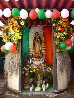 Viva Mexico! Viva Guadalupe!  A devotional niche with a statue of OurLady of Guadelupe, surrounded by flowers, candles, and celebratory balloons placed on Cinco de Mayo, Mexico's Independence Day.
