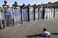 l'umanità in crisi Baby profuga gattona davanti agli agenti con gli scudi. Unaltra foto simbolo della crisi migratoria