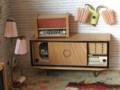 A 1950s Kibri roombox furnished with a combination TV / radio, another radio, a double wall light and a double standard lamp.