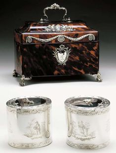 A PAIR OF GEORGE III SILVER TEA CADDIES WITH SILVER-MOUNTED TORTOISE SHELL CASE** London, 1771, Mark T.I.  Each oval, engraved with ribbon and laurel leaf border, with scenes of Chinese figures in exotic landscapes, one harvesting melons, another holding bells, the hinged cover applied with flower sprig finial, the body engraved with a crest, one with silver-gilt interior, one lead lined, with contemporary tortoise veneered case with silver mounts, the applied central cartouch
