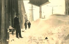 A man, hands in pockets, stands under a large sign marking the location of an automotive garage after the great November 1913 blizzard. Twenty feet down the the sidewalk, two men in winter hats and coats stand in ankle-deep snow. Snow drifts five or six feet deep form a barrier between the sidewalk and the street.