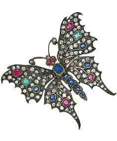 A late 19th century gem-set butterfly brooch Mounted en tremblant, the body set with oval and circular-cut sapphires, between outstretched wings set with rose-cut diamonds, oval and circular-cut rubies, oval-cut sapphires and step-cut emeralds, to cabochon ruby eyes and rose-cut diamond antennae, mounted in silver and gold, circa 1880/90, 5.5cm wide