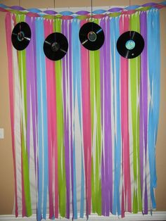 Back drop for my 80's theme photo booth. Made with variety colors of streamers. Old records hanging from the ceiling add that extra something! Can also use old cassette tapes!