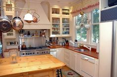 This adorable cottage kitchen may be small, but it's very cozy and has an impressive natural wooden island.