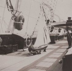 Alexsei crouches behind his toy yacht - onboard the Standart.