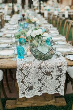 Pop of turquoise blue pressed glassware with lace table runner and metal terrariums holding succulents
