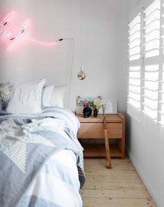 // add something unexpected above your bed - like a pink neon sign in sleek font