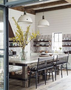 an eclectic farmhouse kitchen boasts tiled walls, industrial pendants, and counter bench seats | home tour on coco kelley