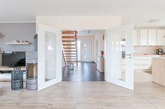 Moderne Flügeltür mit Glaselementen zwischen Eingangsbereich und dem offenen Wohnbereich