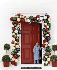 Christmas entry with ornament garland, topiaries, glossy red door