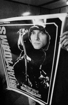 Kurt Cobain poking his head through a Bryan Adams poster in Stockholm, 1992.