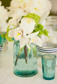 Something like this with the flowers in your colors for centerpieces?
