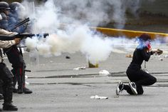 Venezuela's national police fire tear gas as an anti-government protester kneels holding a rock during riots in Caracas April 6, 2014 REUTERS/Carlos Garcia Rawlins