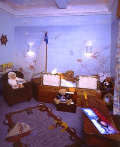 Sail Away #1  A seaworthy, classic, custom crafted sailboat bed is the focal point of this nautical boy's bedroom. Complete with mast, flag, brass fittings and canvas guardrail. The bed also provides storage in both the front and rear of the boat. The mural reflects play at the beach, fish, other boats and a mermaid.