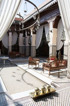 The beautiful Moroccan central courtyard with fountain and wooden garden furniture at the Royal Mansour hotel, Marrakech, Morocco