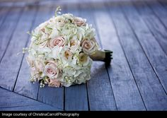 The bridal bouquet will be a clutch of cream hydrangeas, pale pink roses, stephanotis with pearls, and white queen anne's lace wrapped in ivory ribbon.