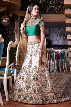 Vintage Wedding Dresses - Emerald green raw silk vintage style blouse with a long ivory heavily embroidered wedding skirt with swarovski diamonds. It comes with gold soft net dupatta and green embroidered border.