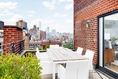 Wood outdoor table and white chairs with a view of New York