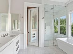 Sleek white bathroom features a water closet with mirrored door next to a walk-in shower finished with a mirrored door under a mirrored flip out window placed in front of a freestanding tub under window.