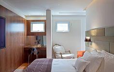 Neste quarto de casal, a cabeceira da cama é composta de placas com tecidos em tons de verde. Repare no cantinho destinado à beleza: o armário de madeira possui nichos para colocar os perfumes e espelho que abre para guardar os produtos de higiene. Projeto da arquiteta Fabiana Avanzi
