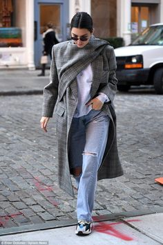 Plaid's the way to do it: Seemingly keen to go under the radar, the supermodel, 22, wrapped up in an oversize grey check coat by Balenciaga for her day in Manhattan