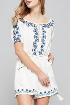 f99a61bb5a63 A floral embroidered off-the-shoulder romper featuring elastic neckline