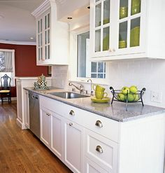 classic, white kitchen cabinets with gray marble countertops and glass panes in the upper cabinets