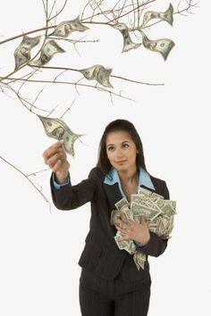 Mujer recogiendo dinero de un árbol - John Lund/Getty Images