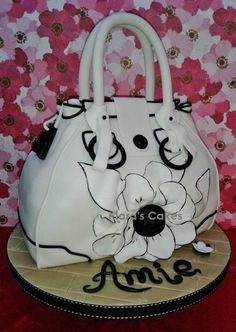 My handbag cake inspired by Jimmy Choo. This cake is chocolate with chocolate frosting. I used 2 × cakes cut in half and then layered and carved. All are edible, including the handles. The black details on the flower are hand-painted.