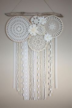 The Large Dream Catcher Wall Hanging has shades of cream and white vintage doilies and beautiful flowers. The hanging consists of different and unique yarn and lace. It also has a one of a kind piece of driftwood at the top that gives it a bohemian look.