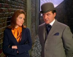 'The Correct Way To Kill' ~ Series 5. Steed wears this pale grey single breasted 3-piece suit with charcoal chalk stripe. A very mod cut, the jacket is fastened with 3 buttons and has two short vents in the skirt, the waist pockets are slanted flaps.  Emma is smartly dressed in an saffron orange dress, with navy jacket  smart black gloves. Accented with saffron orange  navy scarf.