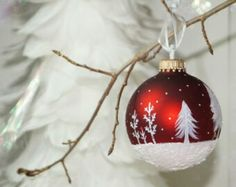 Hand-painted red metallic glass globe ornament with white snowy trees