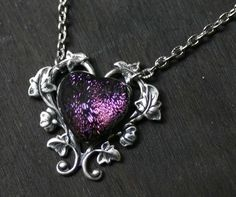 """""""A dichroic glass heart cab is framed by a morning glory vine."""" (Taken from the item description on Top Hatter)"""