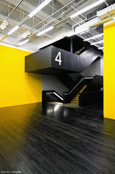 Black, wooden floor against bright yellow accent wall and a floating stairwell. This is awesome.